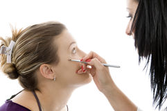 Model getting eye makeup from beautician. Against white background Stock Images