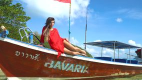 Model girl lies on a longtail boat standing next to the beach and posing. Model girl in a red dress lies and posing on a longtail boat with Thai flag on it stock video