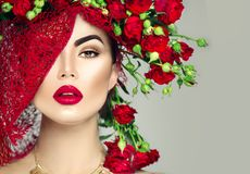 Model girl with red roses flower wreath and fashion makeup. Flowers hairstyle