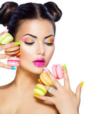 Model girl taking colorful macaroons Royalty Free Stock Photos