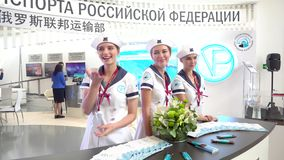 Model girls pose against the backdrop of the stand of the Ministry of Transport of the Russian Federation. September, 2018 - Vladivostok, Russia - Model girls stock footage