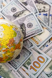 Model globe on spread US dollar banknotes. Model globe is placed on spread US dollar banknotes Stock Photo