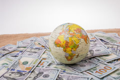Model globe on spread US dollar banknotes. Model globe is placed on spread US dollar banknotes Royalty Free Stock Photos