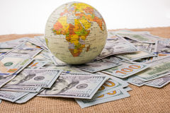 Model globe on spread US dollar banknotes. Model globe is placed on spread US dollar banknotes Royalty Free Stock Images
