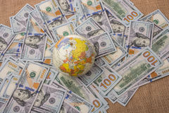 Model globe on spread US dollar banknotes. Model globe is placed on spread US dollar banknotes Stock Image