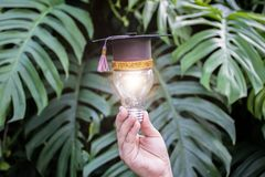 Model graduation cap. Put on the bulb child is holding. stock photos
