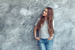 Model in gray t-shirt over street wall. Young beautiful model wearing blank gray t-shirt and jeans posing against rough concgrete wall, minimalist street fashion Royalty Free Stock Photo