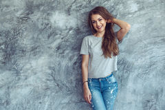 Model in gray t-shirt over street wall. Young beautiful model wearing blank gray t-shirt and jeans posing against rough concgrete wall, minimalist street fashion stock images