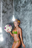 Model in a green knitted bikini with bouquet of white flowers Stock Images