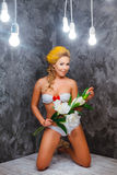 Model in a green knitted bikini stay with bouquet of flowers Royalty Free Stock Image