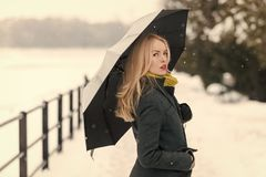 Model in grey coat, scarf and mittens. Christmas and new year. Holidays celebration concept. Girl walking with umbrella on winter day. Woman with long blond royalty free stock photo