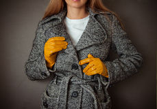 Model in grey coat and yelloy leather gloves Royalty Free Stock Photos