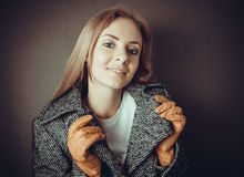 Model in grey coat and yelloy leather gloves Stock Image