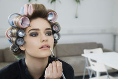 Model In Hair Curlers Applying Lip Gloss Royalty Free Stock Photo
