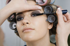 Model in Hair Curlers Having Makeup Applied Stock Photos