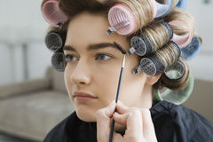 Model in Hair Curlers Having Makeup Applied Stock Image