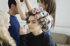 Model in Hair Curlers Having Makeup Applied Royalty Free Stock Image