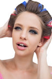 Model with hair curlers touching her hair Royalty Free Stock Photography