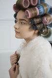 Model in Hair Curlers Wearing Fur Coat Stock Photo