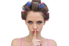 Model in hair rollers posing with finger on mouth. Model in hair rollers posing with her finger on the mouth on white background Royalty Free Stock Image