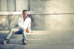 Model handsome man relaxed sitting on the steps of white marble. Italian beautiful male sitting on the steps of the ancient white marble. Wearing white shirt Royalty Free Stock Photo