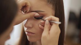 Model have a makeup by makeup artist in beauty salon. First person view. Redhead model with freckles. Close up of model stock footage