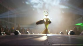 Model with a headdress in yellow dress with feathers pose on catwalk in smoke and light of lamps on defile stock video footage