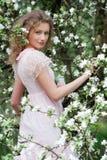 Model in het roze kleding stellen in witte bloemen Royalty-vrije Stock Afbeeldingen