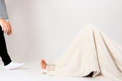 Model hiding under cover in photo studio Royalty Free Stock Image