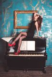 Model in high heels on piano Royalty Free Stock Image