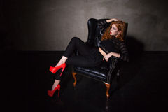 Model in high heels sitting on black chair Stock Photography