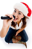 Model holding karaoke and wearing christmas hat Stock Photography