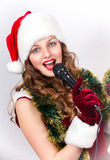 Model holding karaoke and wearing christmas hat Stock Images