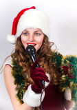 Model holding karaoke and wearing christmas hat Royalty Free Stock Photography