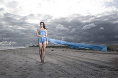 Model holding long blue dress. Pretty model holding long blue dress on the beach. Windy and cloudy summer weather Stock Images