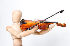 Model holding violin close up. Model is make of wood and is often used for drawing art. Model can represent any ethnicity or gender Royalty Free Stock Images