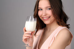 Model holding a wine glass of milk. Close up. Gray background Stock Photos