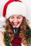 Model holdingskaraoke en het dragen van Kerstmishoed Stock Afbeeldingen