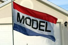 Model Home. A model home depicted in a cropped view of a home with a red, white and blue flag out front that reads Model.flag Stock Photo