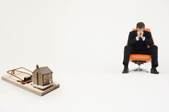 Model home on mouse trap with worried businessman sitting on chair representing increasing real estate rates Royalty Free Stock Images