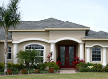 Model Home in Suburbs. Model home with formal red door,columns and arched windows, and tropical landscaping stock photo