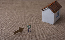 Model house and an arrow beside a man figure Royalty Free Stock Photography