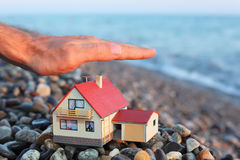 Model of house on beach, Man's hand over house Royalty Free Stock Photos