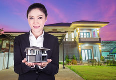Model house in business woman hand with actual house and garden. Bacground Stock Photos