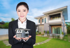 Model house in business woman hand with actual house and garden. Bacground Stock Photo