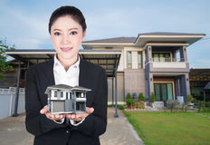 Model house in business woman hand with actual house and garden. Bacground Stock Images