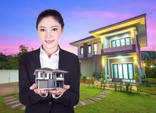 Model house in business woman hand with actual house and garden. Bacground Stock Photography
