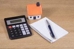 Model house, calculator and notebook with pen Royalty Free Stock Image