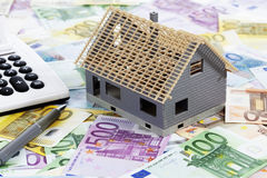 Model house with calculator and pen on heap of euro notes Stock Photo