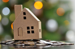 Model of house with coins on wooden table Royalty Free Stock Photography